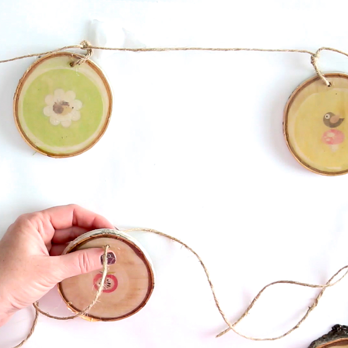 Stringing and tying together wood slices for a DIY garland