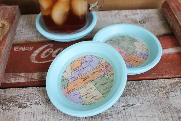 Make these DIY map coasters for your home! Use terra cotta saucers for coasters that look great indoors or out!