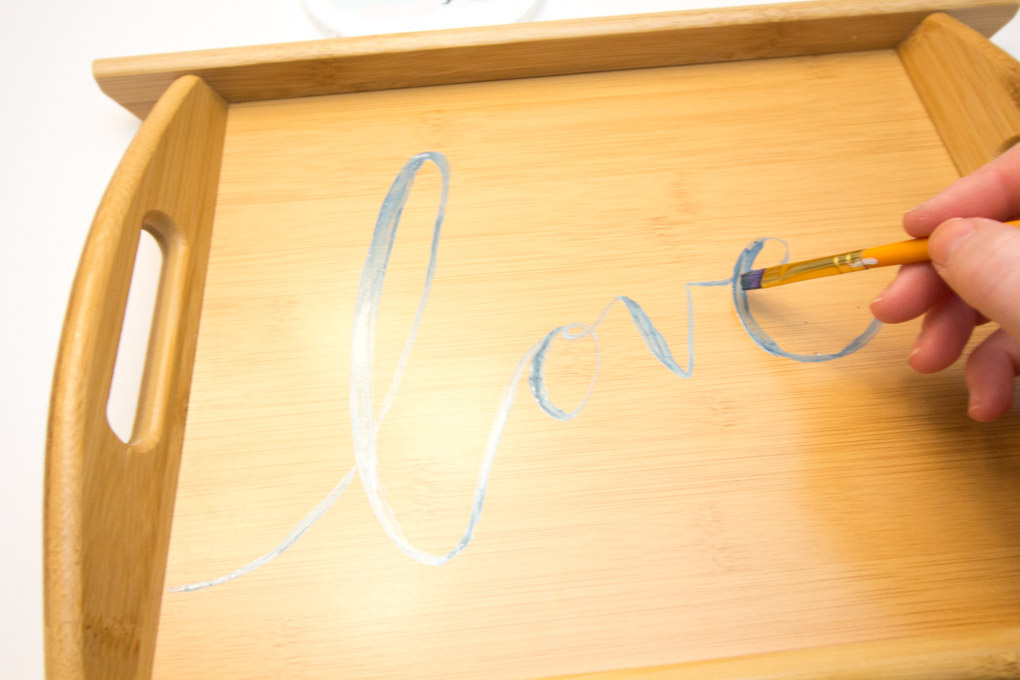 Handlettering the word love onto a wooden serving tray using blue metallic paint