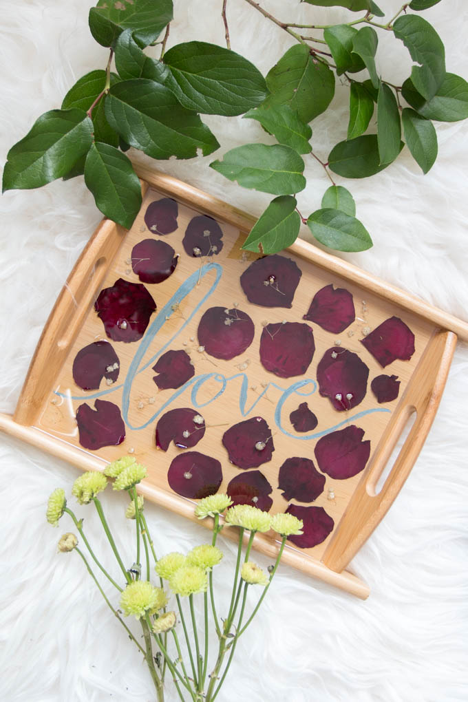 A wooden pressed petal serving tray arranged on a sheepskin rug surrounded by greenery