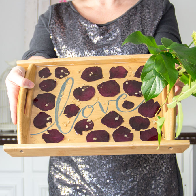 Woman holding wooden pressed petals serving tray