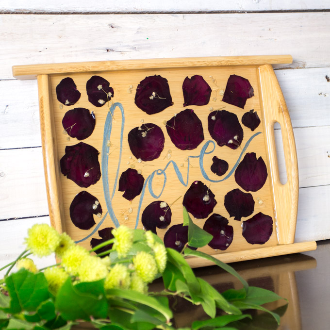 A wooden serving tray with embedded rose petals and baby's breath leaning against a plank wooden wall