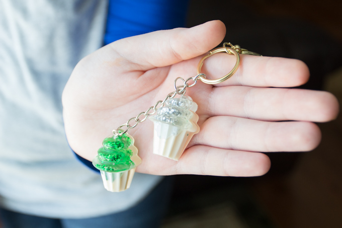 Girl holding a key chain with green and silver resin cupcake charms