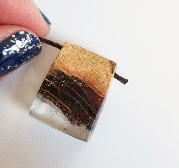 Necklace cord through wood