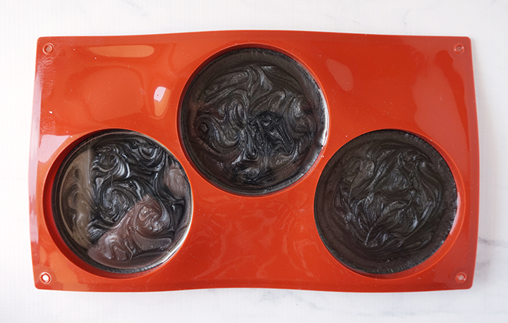 Black resin mixture in coaster mold