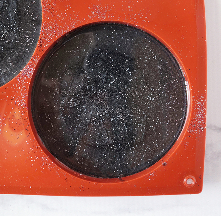 Layer of Clear Resin with Micro beads over black resin coaster