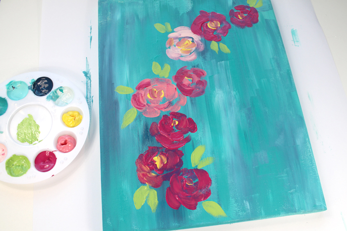 Step 2: Second layer of Flowers Then paint a row of big, chunky flowers on the canvas. These flowers are very splotchy and random. Leave gaps of background colors between the blobby petals. Add green leaves. Do not strive for perfection here, keep them very abstract.