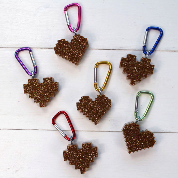 Make pixel heart glitter resin keychains as the perfect Valentine day handout. These keychains are perfect for keeping track of keys, hooking on a zipper or adorning a backpack.