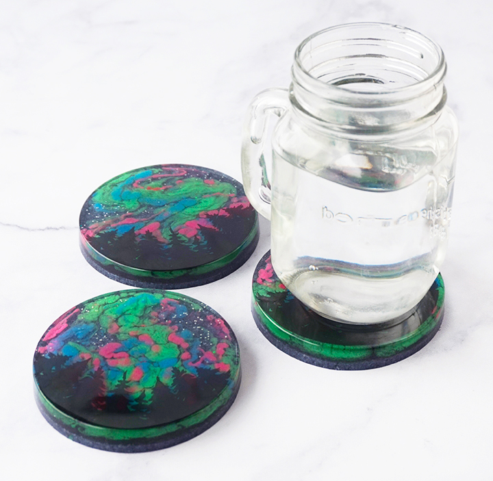 Northern Lights Resin Coasters with Glass of Water