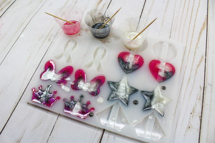 To make DIY resin straw toppers, pour three colors of resin into the silicone straw topper mold.