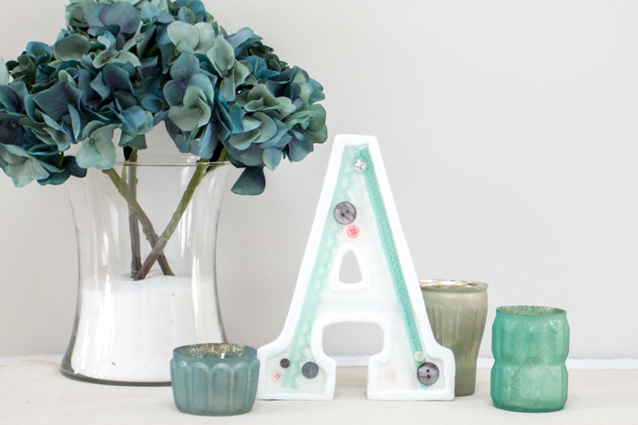 Make your own DIY monogram decor! Use lace, buttons and a wood letter to create a beautiful shabby chic monogram for your gallery wall, nursery or wedding decor.