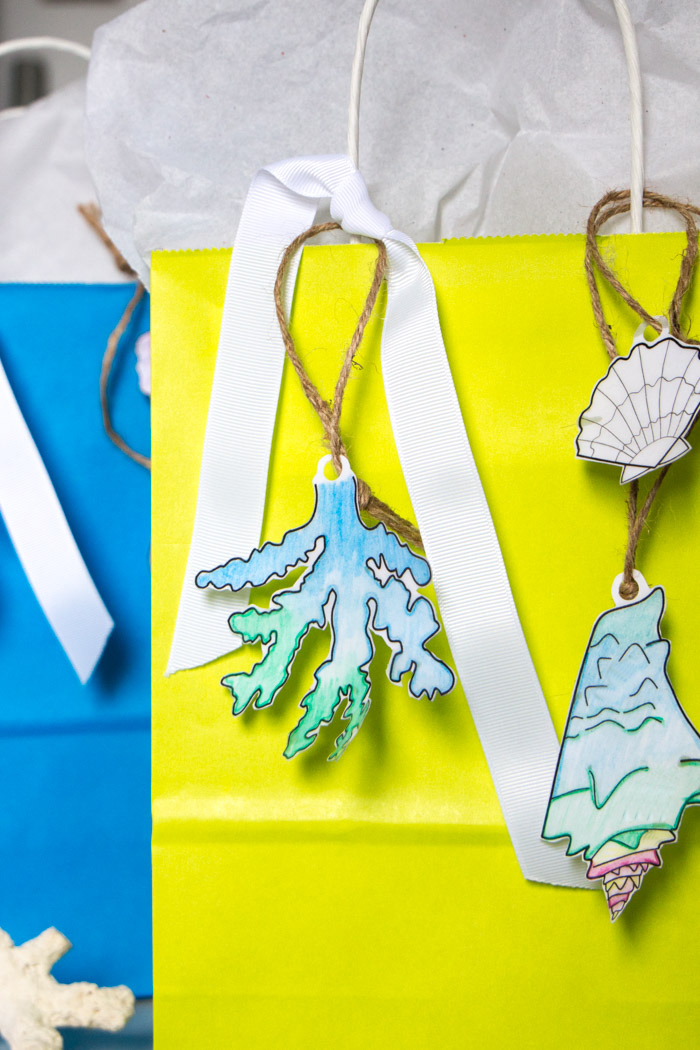A fun craft idea to make your own paper embellishments with any coloring page and resin. They're great for a coastal wedding, bridal shower, gift tags and more. DIY tutorial included!