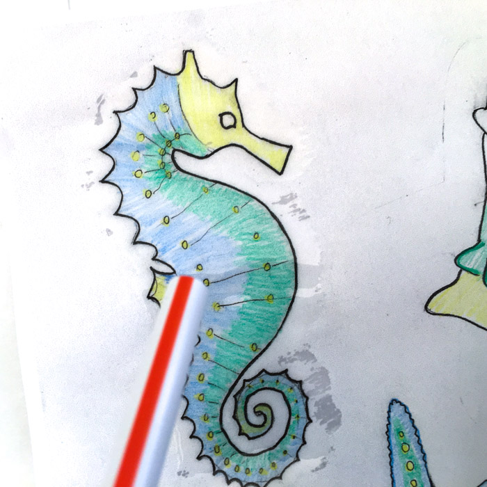 Remove air bubbles from paper embellishments by blowing through a straw