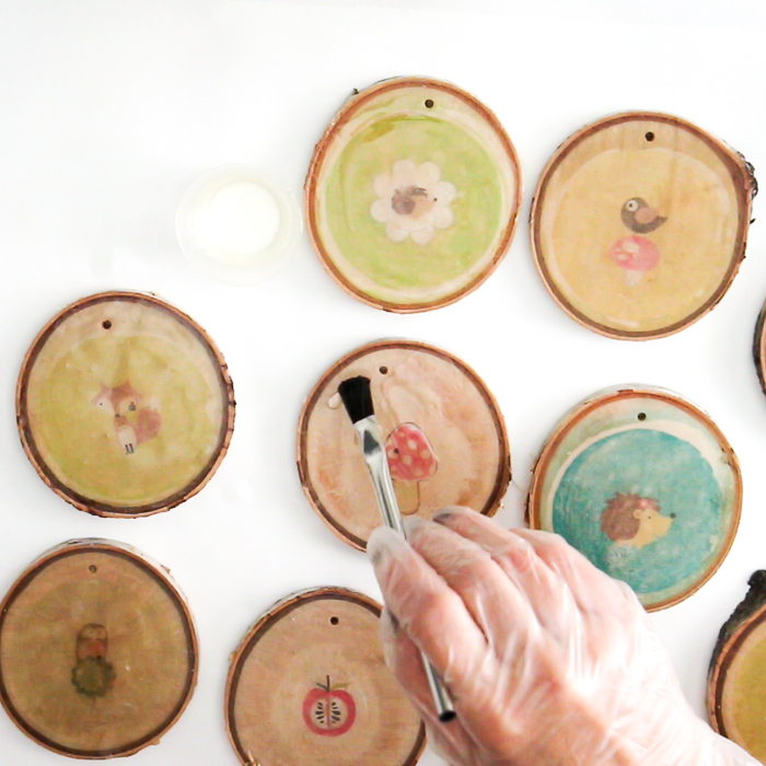 Applying easy cast epoxy resin to wood slice surfaces. DIY woodland nursery decoration.