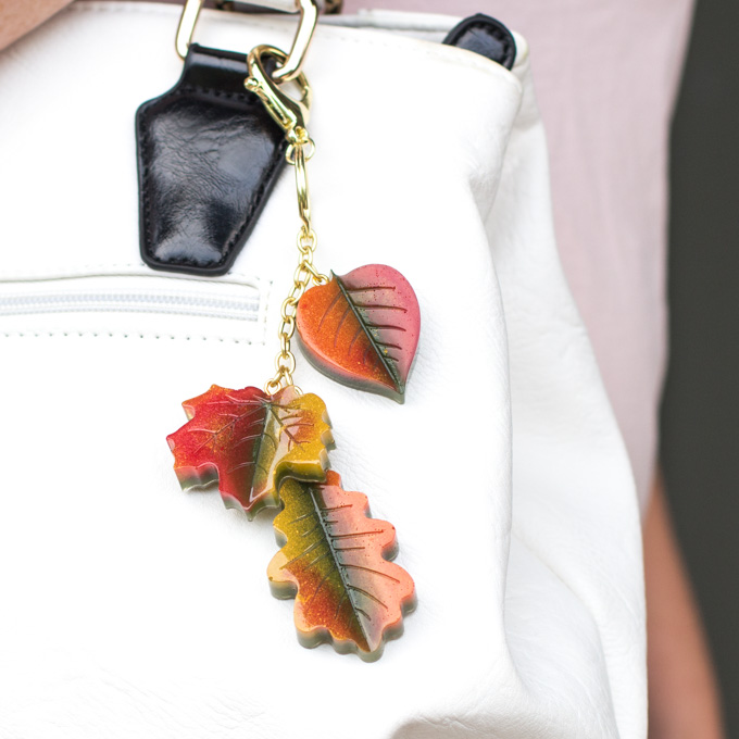 Three resin leaves connected together on a gold chain, hanging on a white purse