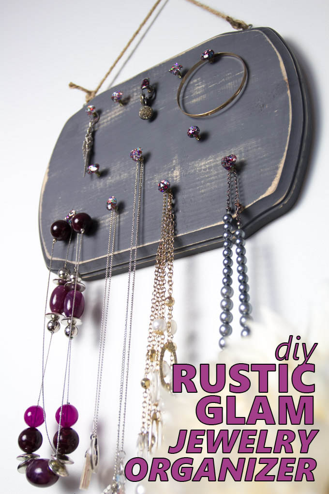 A distressed gray wood jewelry organizer hanging on a wall with jewelry
