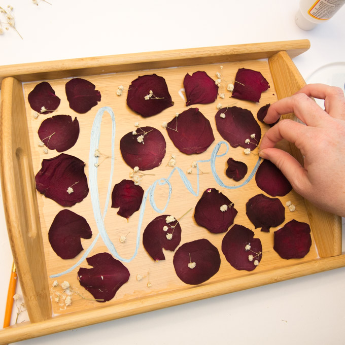 Arranging and pasting pressed rose petals and dried baby's breath onto a wooden serving tray