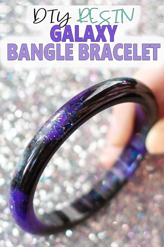 Close up image of galaxy themed resin bracelet against a glittering silver background.