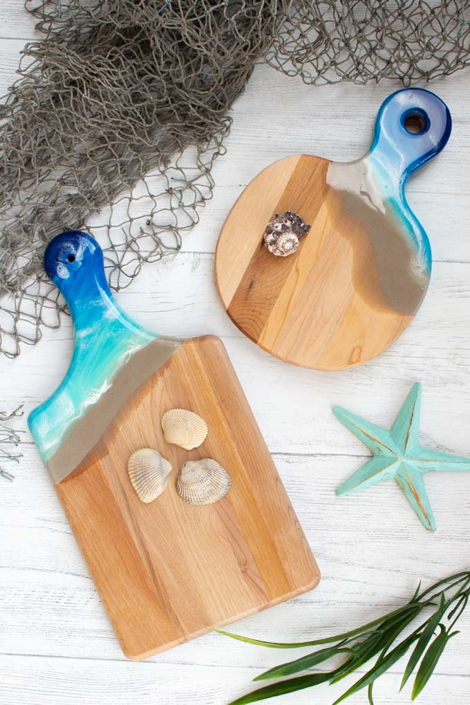 Two wood cutting boards with handles embellished with resin in a beach theme.