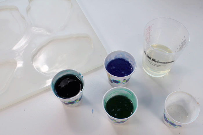Step 2: Mix Agate Slice Color Then add about 4 drops of blue dye in one cup. Next, 4 drops of green dye in another cup. Then mix 2 drops of blue and 2 drops of green in the third cup. Add some white pigment in the last small cup and leave the mixing cup with clear resin.