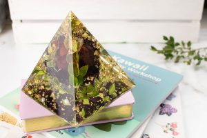 Resin pyramid with embedded rose, gold foil and boxwood leaves on a stack of books.