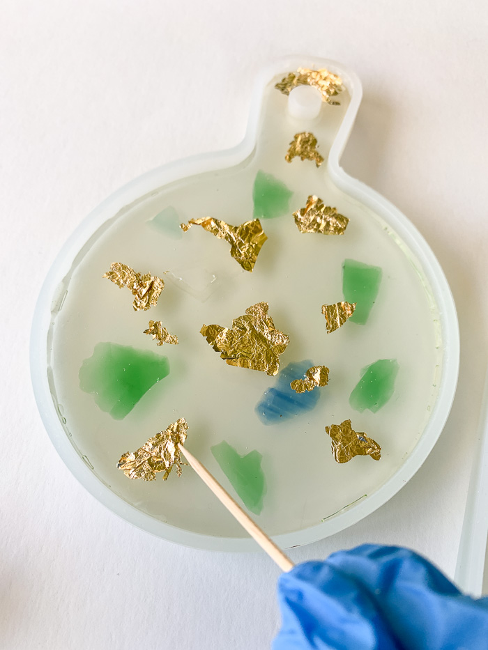 Place gold leaf flakes into the soft resin, and gently push the flakes down with a toothpick.