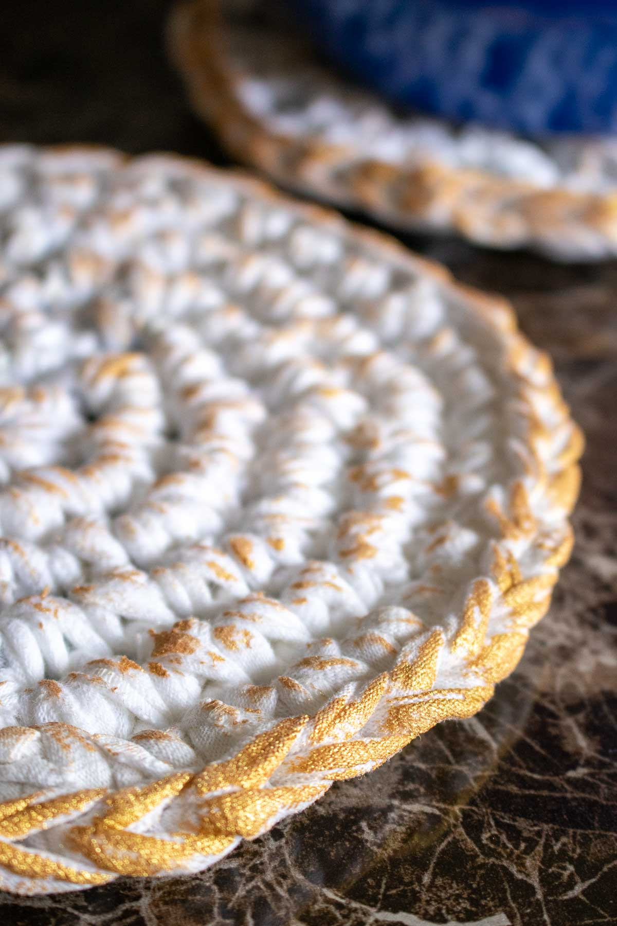 Close up image of the edge of the gold-painted t-shirt yarn heat pad.