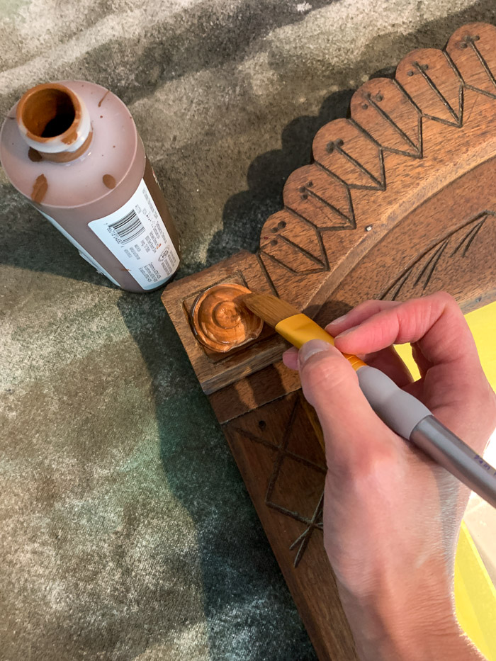 Painting the resin applique the same color as the furniture piece helps it blend in.