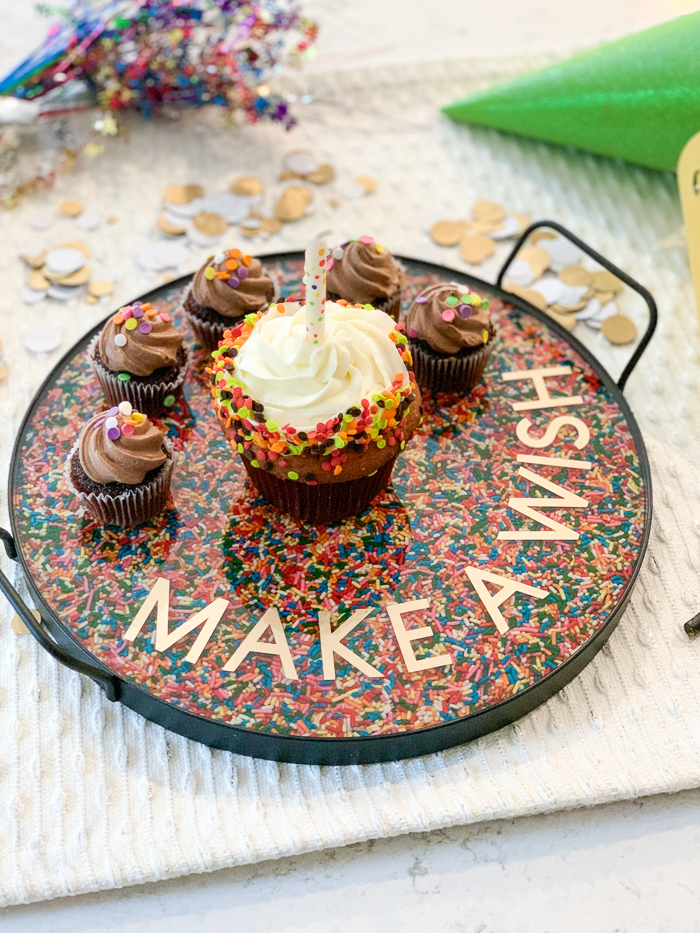 Learn how to make a DIY rainbow sprinkles resin tray with this fun tutorial! EnviroTex Lite pour over resin makes it easy to create a festive serving tray for birthday cakes or cupcakes. They sit atop a layer or rainbow sprinkles!